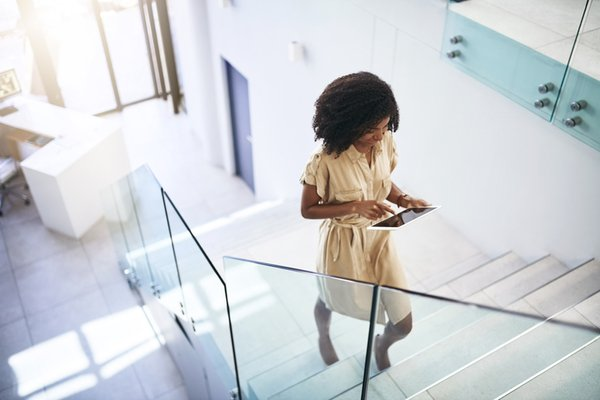 female walking up stairs on tablet