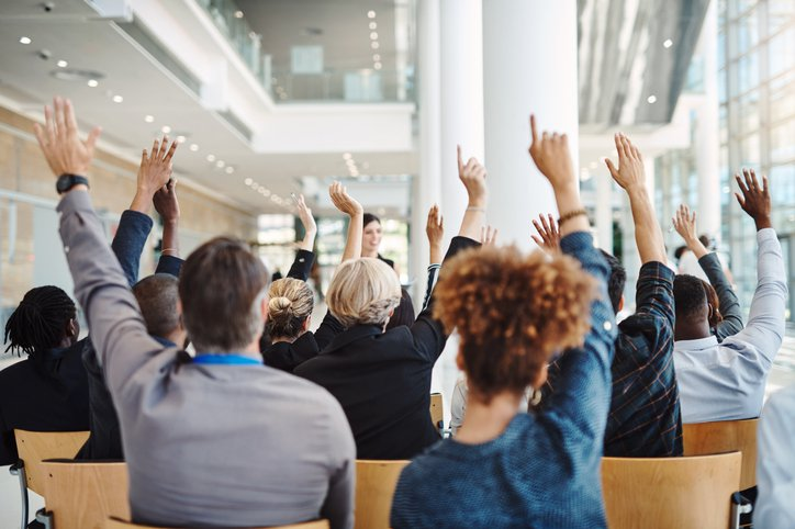 businesspeople raising their hands to ask questions