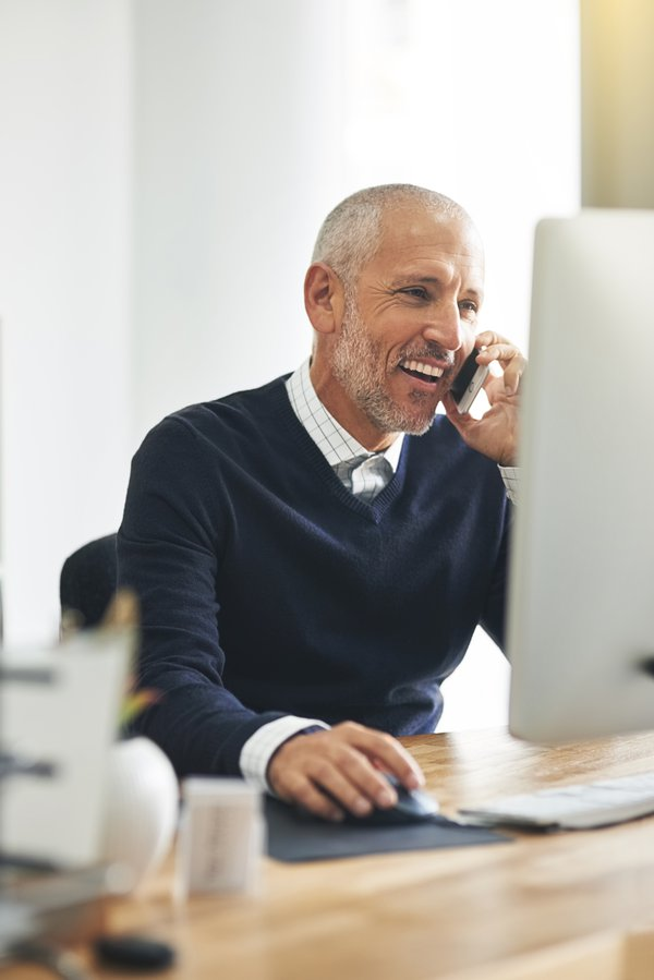 Male talking on phone while on computer