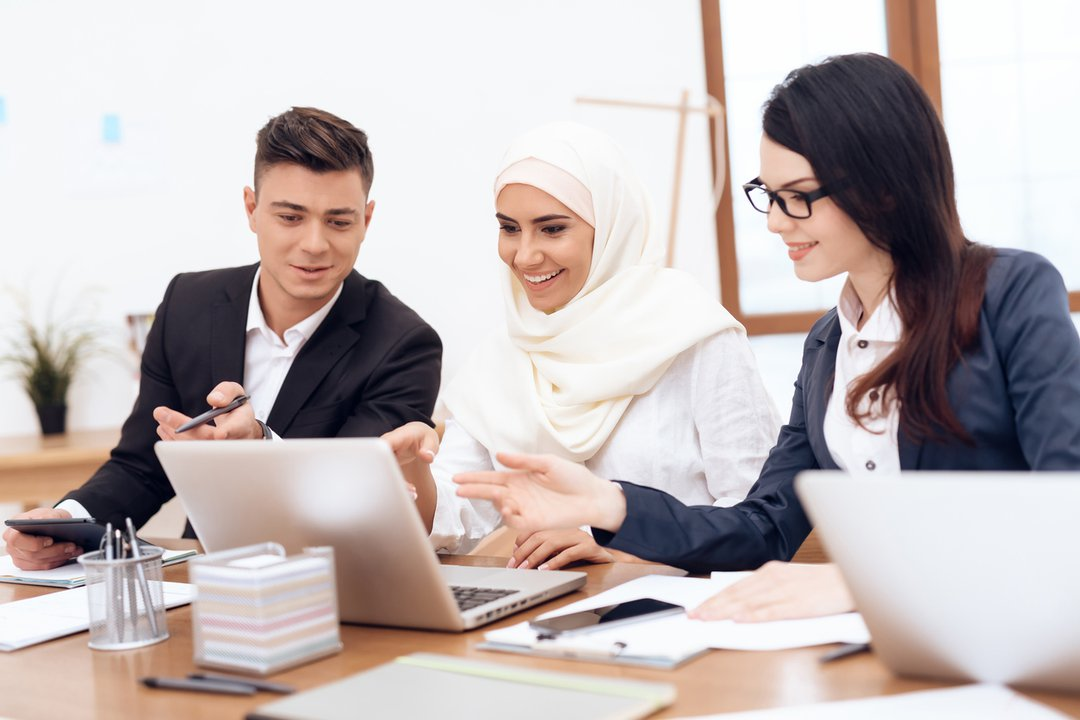 Woman in hijab works in the office with her colleagues.