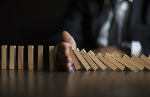 Businessman Stop Domino Effect. Risk Management and Insurance Concept
