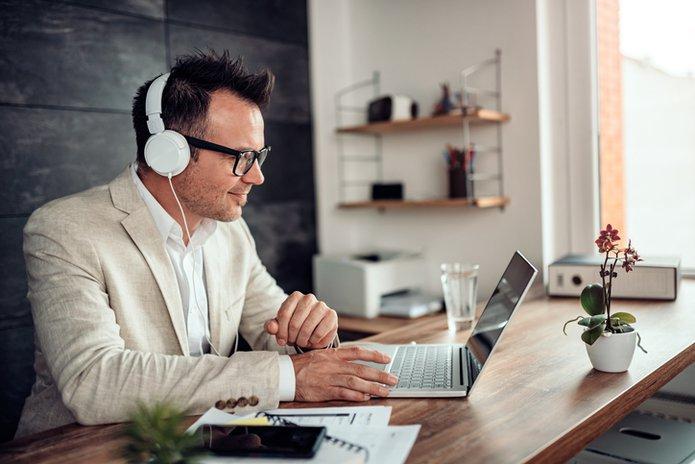 Businessman using laptop and listening music on headphones eLearning