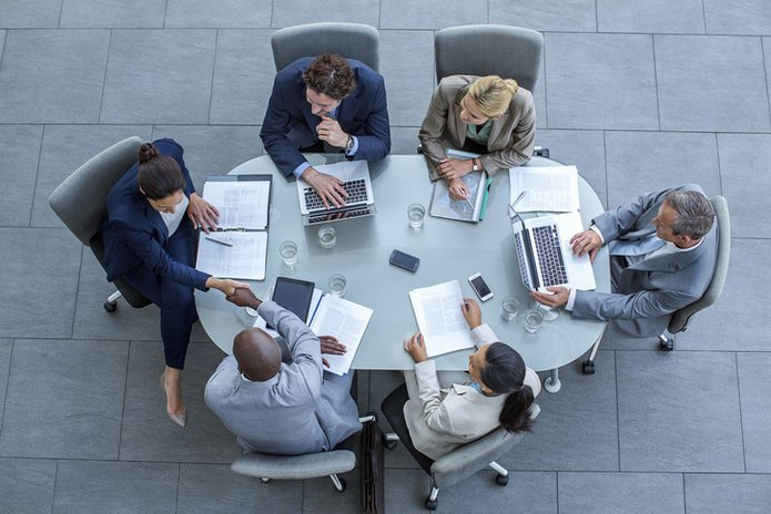 Businesspeople shaking hands at conference table