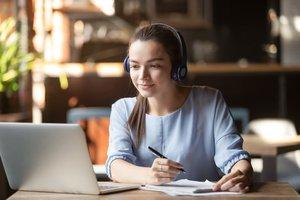 Focused woman wearing headphones using laptop, writing notes